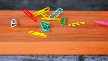 Colorful office paper clips falling down in slow motion video