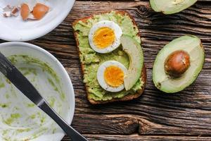 Toast with mashed avocado and eggs on messy rustic wooden table photo