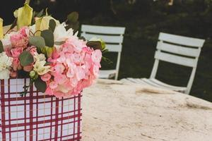 Flowers in gift box outside on table photo