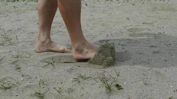 close-up van benen die op zand lopen en zand schoppen slow motion video