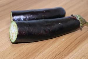 Berenjena de color violeta sobre la mesa de madera para cocinar foto