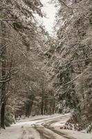 camino de nieve de invierno frío a través de las montañas foto