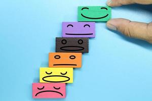 Colorful wooden blocks with emotion face. Customer evaluation and satisfaction concept. photo