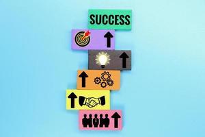 Piedras de colores con iconos de negocios específicos y el concepto de éxito. foto