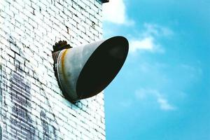 Air conditioning tube cut in diagonal sticking out of the white brick wall on blue sky with clouds photo