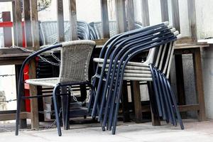Stacked chairs near cafe tables standing on street photo