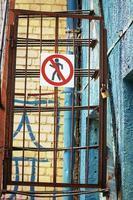 No walking sign on rusty iron fence foor near blue textured wall photo