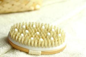 Wooden natural brush for dry skin massage on white towel photo