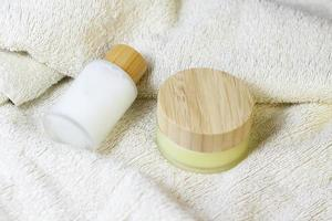 Wooden natural brush for dry skin massage on white towel with cosmetic crystal bottles with wooden bamboo top photo