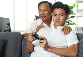 Father and son playing video games at home on vacation happily photo
