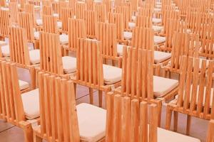 Sillas de madera en una fila en una iglesia. foto