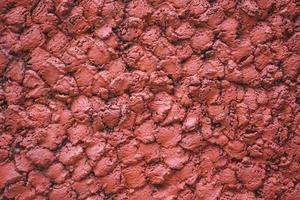 Abstract concrete red wall textures background. Background of a red stucco coated and painted exterior photo