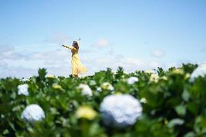 Happy Asian woman holds her hand in a field of Hydrangea flowers photo