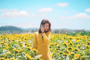 Mujer asiática alegre con hermoso campo de girasol, concepto de viaje de verano foto