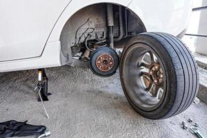 Car mechanic changing tire, changing tire with wheel wrench. photo