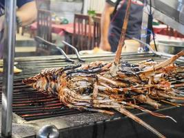 Grilled Lobster on a gridiron over fire at the seafood night market, Grilled prawns and lobster on the grill at Night Market in Hua Hin, Thailand photo