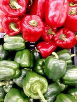 pimientos verdes y rojos. una gran cantidad de pimientos en una pila, fondo natural foto
