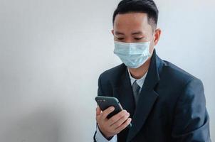 Business men wear face masks to watch mobile phone photo