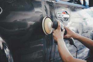 detalle del coche: hombre que trabaja en el pulido y el cuidado del exterior con cera. pulido automático con máquina foto