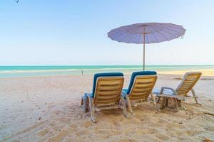 Empty beach chair on sand with ocean sea background photo