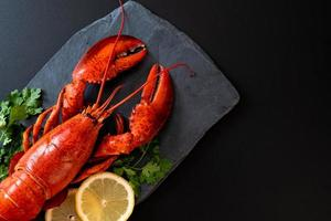 Red lobster with vegetable and lemon on black slate plate photo