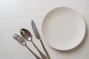 Empty plate or dish with knife, fork, and spoon on wood tile background photo