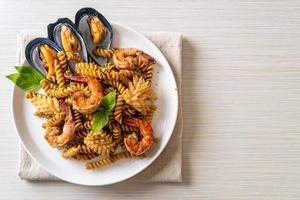 pasta en espiral salteada con salsa de mariscos y albahaca - estilo de comida fusión foto