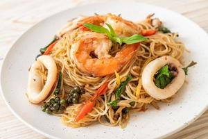fideos chinos salteados con albahaca, chile, camarones y calamares - estilo de comida asiática foto