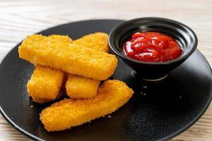 Palitos de pescado frito crujiente con pan rallado servido en un plato con salsa de tomate foto