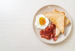huevo frito con pan tostado y tocino para desayunar foto