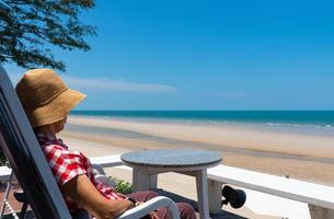 Senior woman sitting on balcony of hotel looking at blue sea and white beach in sunny day of summer vacation photo