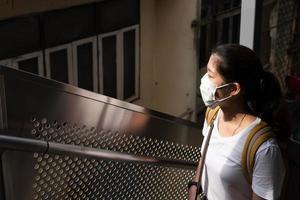 joven y bella mujer asiática con mascarilla como pauta de distanciamiento social. ella está usando la escalera mecánica para subir a la estación de tren del cielo. nuevo estilo de vida normal, covid-19, concepto de coronavirus foto