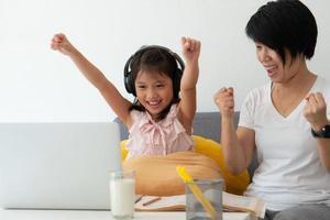 una madre asiática está enseñando a una hija pequeña de la lección de computación en línea como educación escolar en el hogar debido a un brote de covid-19 o coronavirus foto