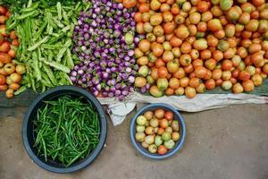 tomates, berenjenas redondas moradas, chiles verdes, frijoles alados en la hoja y en la palangana se vendían en el mercado foto