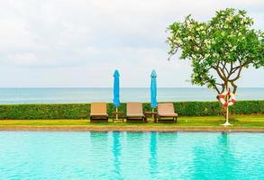 Chair pool and umbrella around swimming pool with ocean sea background photo