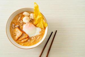 Rice vermicelli noodles with meatball, roasted pork and egg in spicy soup photo