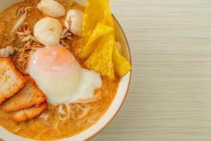fideos de arroz con albóndigas, cerdo asado y huevo en sopa picante foto