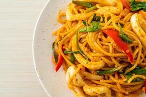 espaguetis salteados con huevo salado y calamares - estilo de comida fusión foto
