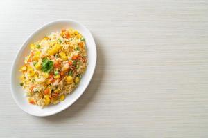 arroz frito casero con vegetales mixtos de zanahoria, guisantes, maíz y huevo foto
