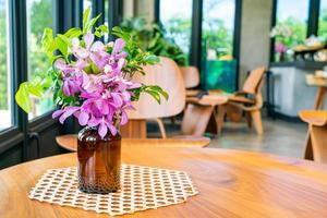 Orchid flowers in vase decoration on table in coffee shop cafe restaurant photo
