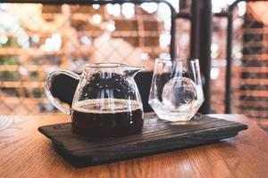 Cold drip black coffee jar with glass and ice in coffee shop cafe and restaurant photo