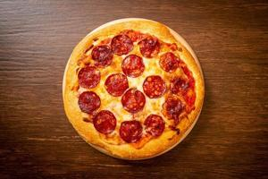 Pizza de pepperoni en bandeja de madera - estilo de comida italiana foto