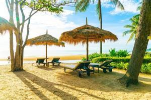 Sombrillas y sillas de playa con palmeras de coco y fondo de playa de mar y cielo azul - concepto de vacaciones y vacaciones foto