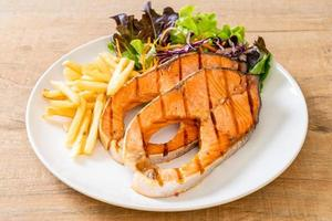Double grilled salmon steak fillet with french fries photo