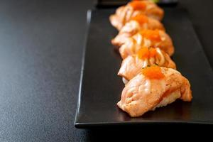 Grilled salmon sushi on black plate - Japanese food style photo