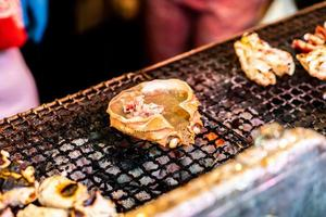 Japanese dish of grilled crab shell with miso called Kani Miso Koura Yaki on a hot grill photo