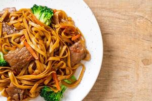 Stir-fried noodles with pork and vegetable - Asian food style photo