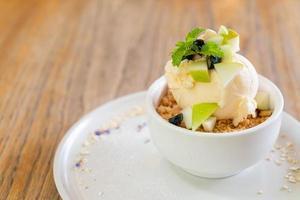 Helado de vainilla con manzana fresca y crumble de manzana en cafetería y restaurante foto