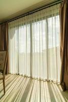 Beautiful curtain with sunlight from glass window photo