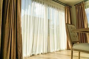 Hermosa cortina con luz solar desde la ventana de vidrio foto
